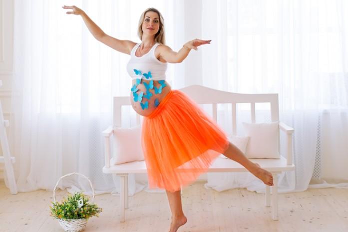 Беременная танцует и улыбается