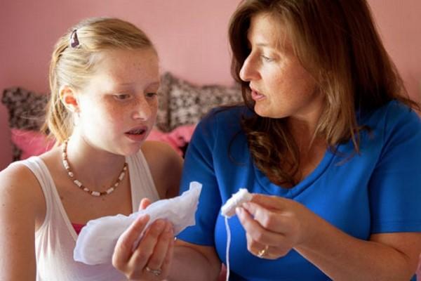 Мать показывает дочери прокладку и тампон
