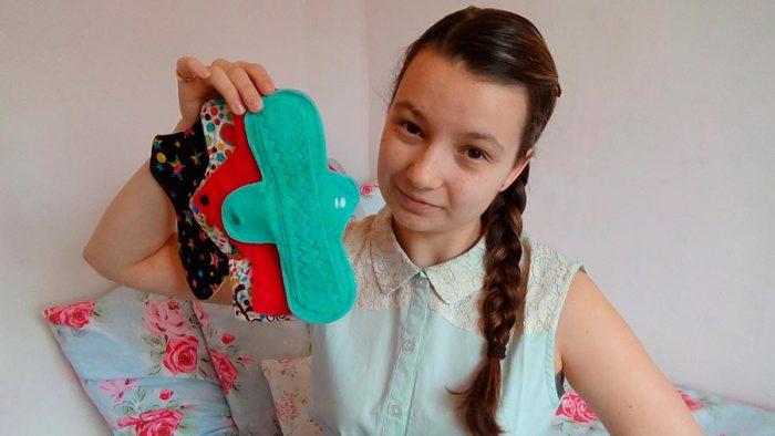 Девочка держит в руках разноцветные прокладки и улыбается
