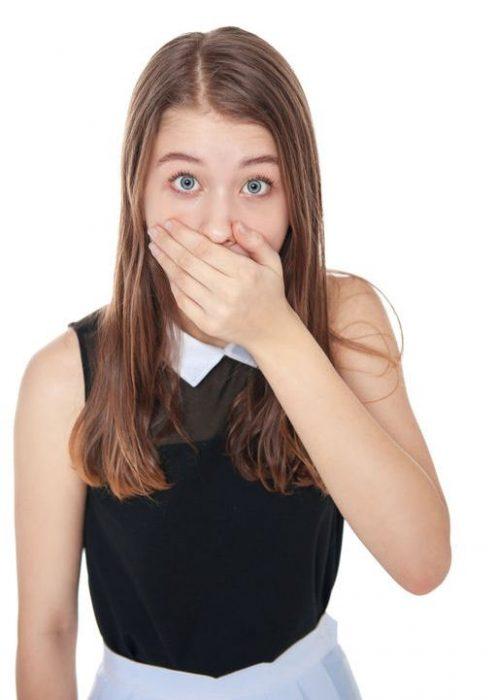 Девочка с испуганными глазами закрывает рот рукой