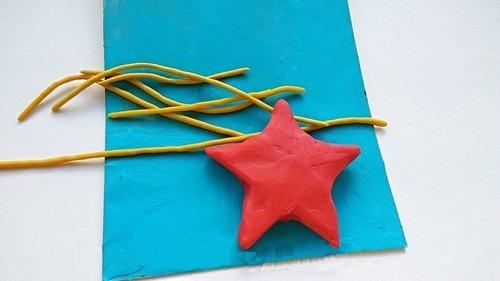 Жёлтые жгутики и звезда из красного пластилина