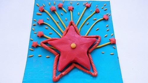 Звезда в центре открытки, её обрамляет красный жгутик, а сверху располагается шлейф салюта