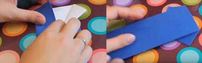 У сложенной заготовки с одного конца отгибаются края; заготовка с другой стороны с получившимися рукавами