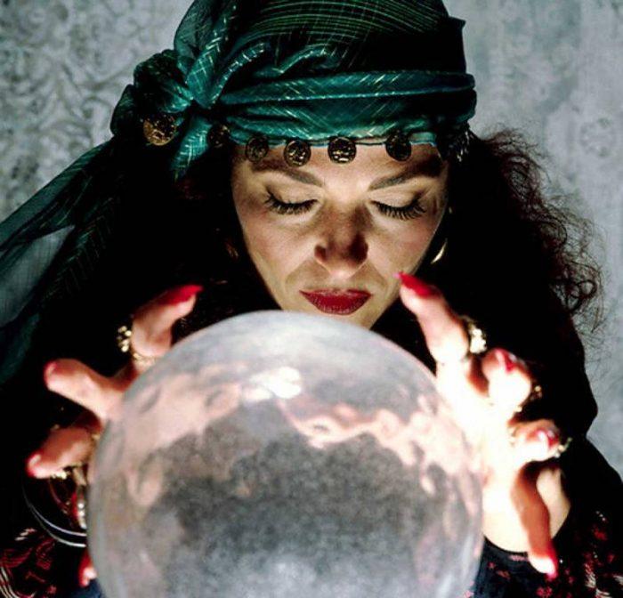 женщина гадалка держит руки над шаром