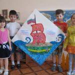 Четверо детей держат огромную открытку, выполненную в технике аппликации мятой бумагой