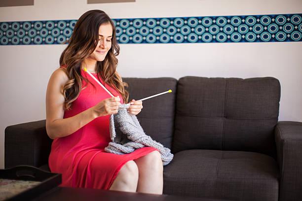 Женщина вяжет, сидя на диване с ровной спиной и согнутыми в коленях ногами
