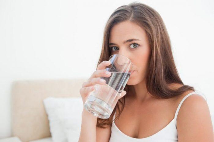 Молодая мама пьет воду