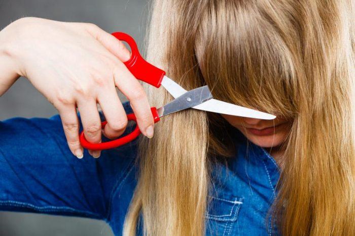 Женщина подрезает себе чёлку