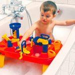 Мальчик купается в ванной и играет на игровом столике