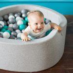 Мальчик сидит в сухом бассейне с шариками