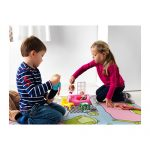 Мальчик и девочка сидят на полу и играют игрушечной мебелью