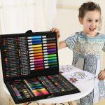 Девочка стоит возле чемоданчика с предметами для рисования