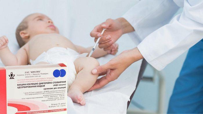 Врач делает ребёнку инъекцию в бедро, на первом плане упаковка вакцины АКДС