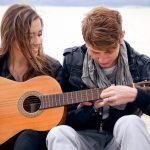 парень учит девушку играть на гитаре