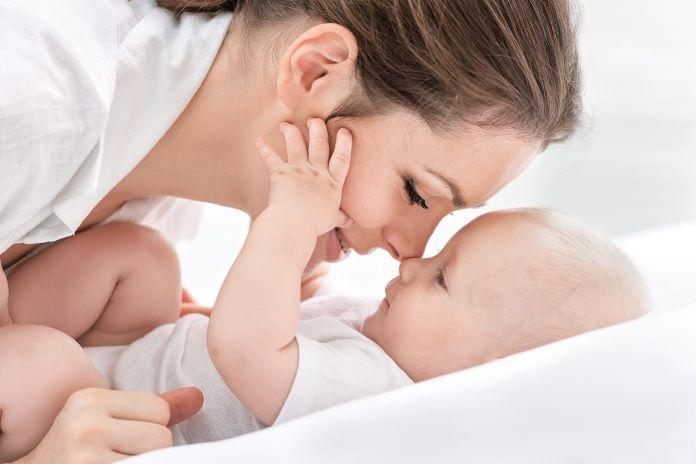 Мама обнимает младенца, но держит её за щёки ручками