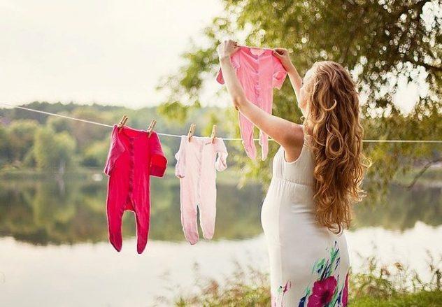 Беременная вешает бельё