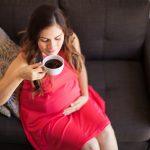 Беременная сидит на диване и пьёт кофе
