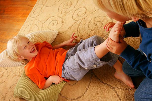 Один мальчик щекочет другого за пятку