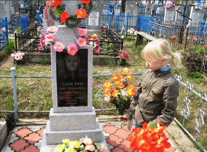 Девочка на кладбище смотрит на могильный памятник