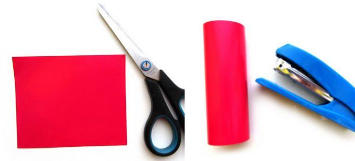 Вырезанный из картона красный прямоугольник; прямоугольник свёрнут в виде цилиндра, рядом степлер
