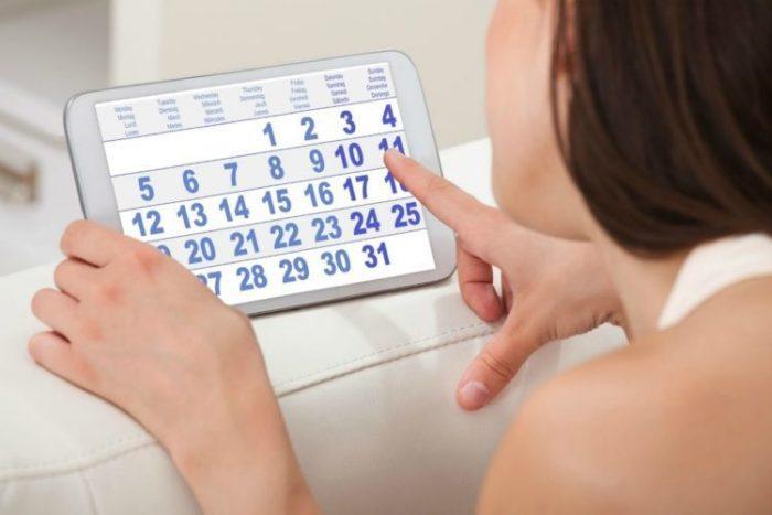 Женщина смотрит на электронный календарь