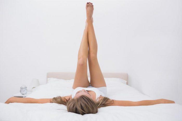 Женщина лежит в кровати, подняв ноги перпендикулярно туловищу