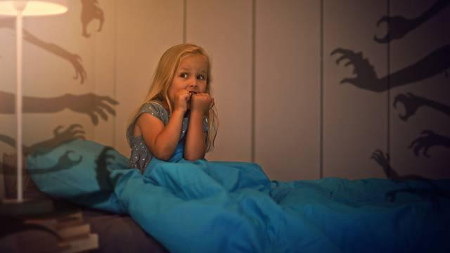 Испуганная девочка сидит на кровати, рядом тени рук