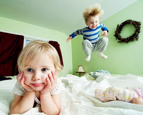 Ребёнок прыгает по кровати, другой лежит на ней