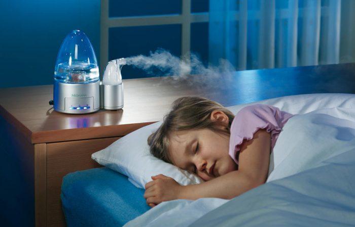 Девочка спит, рядом с кроватью находится увлажнитель воздуха