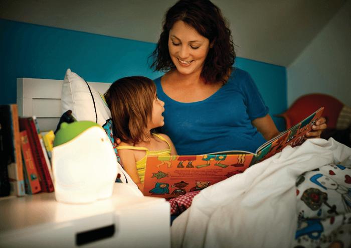 Мама читает ребёнку в кровати книжку