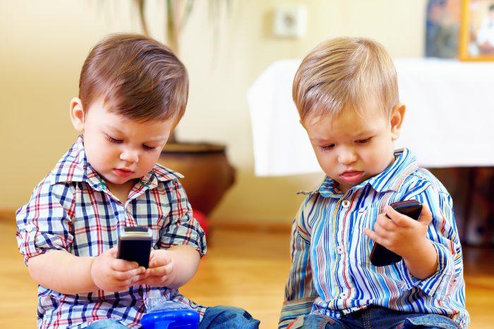 Два мальчика (младших дошкольника) держат в руках мобильные телефоны
