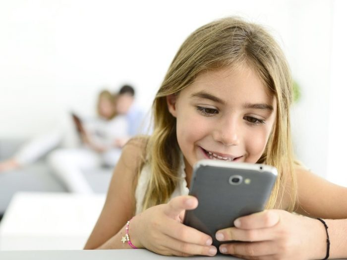 Девочка увлечённо смотрит в смартфон