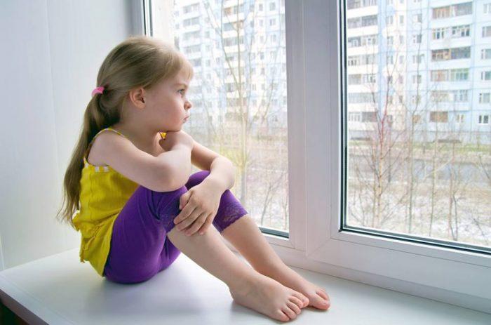 Девочка сижит на подоконнике и задумчиво смотрит в окно