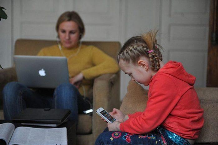 Девочка сидит в телефоне, на заднем плане мама занимается с ноутбуком