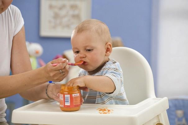 Женщина кормит младенца пюре из баночки