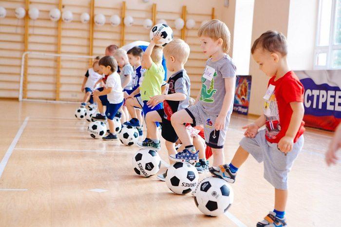 Мальчики-дошкольники с мячами в футбольной секции
