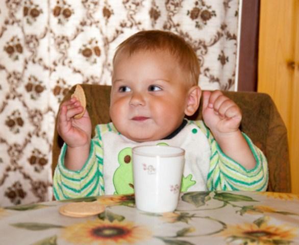 Годовалый малыш ест печень, рядом стоит кружка