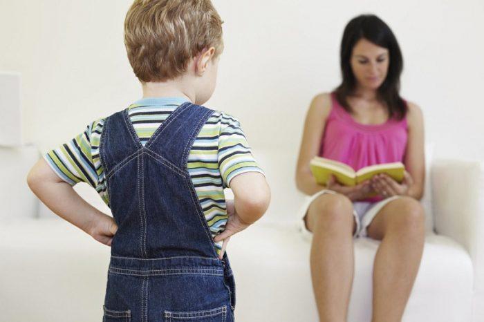 Мама сидит на диване, читая книгу, не обращая внимания на ребёнка