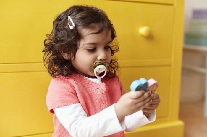 Девочка примерно двух лет с соской во рту