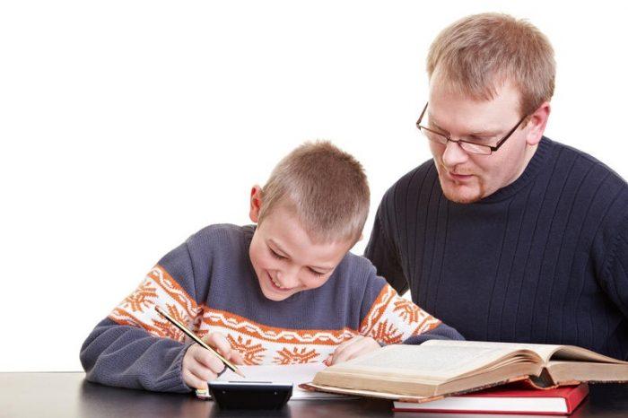 Мальчик сидит с тетрадью и учебниками, рядом с ним мужчина