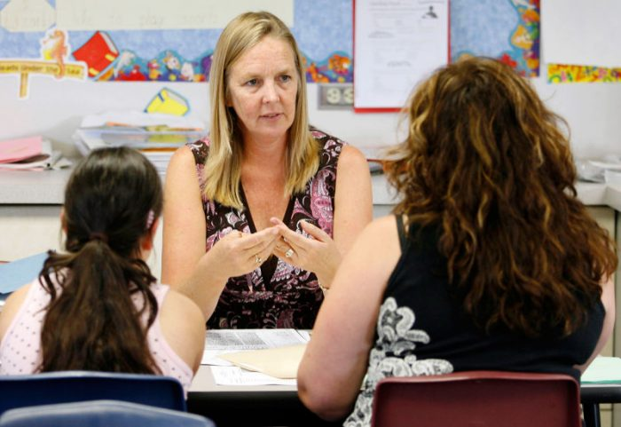 Мама беседует с учителем, за столом также сидит девочка