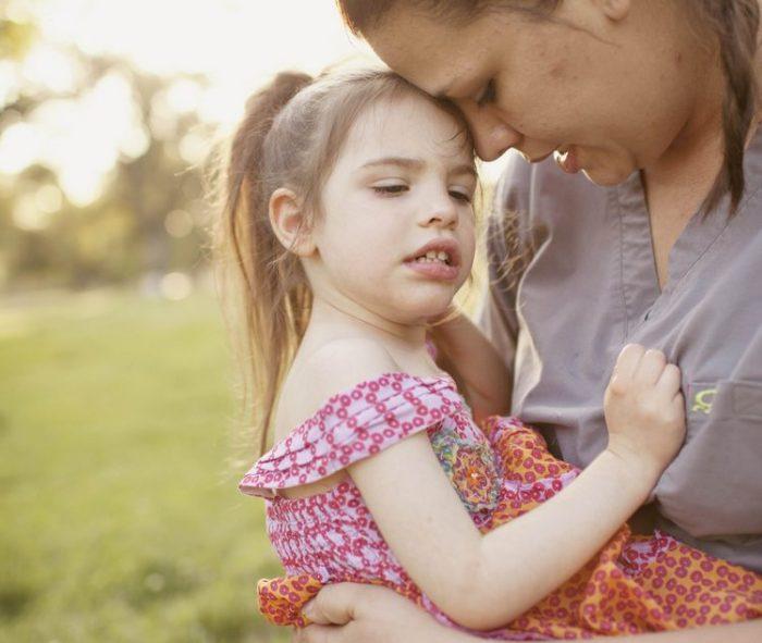 Женщина держит на руках больную девочку