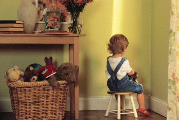 Девочка сидит на стуле, отвернувшись к стене