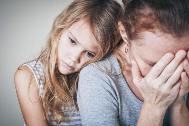 Женщина закрыла лицо руками, девочка её обнимает