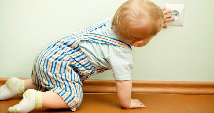 Маленький мальчик собирается сунуть пальчики в розетку