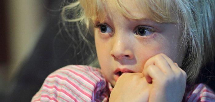 Испуганная девочка держит пальцы во рту