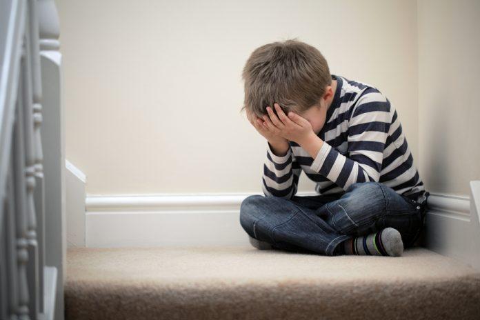 Мальчик сидит на кровати и плачет