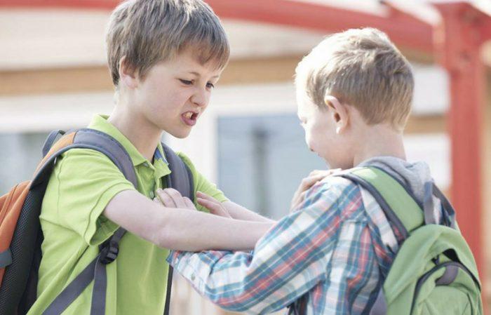 Мальчик нападает на другого — хватает его за плечи со злым выражением лица