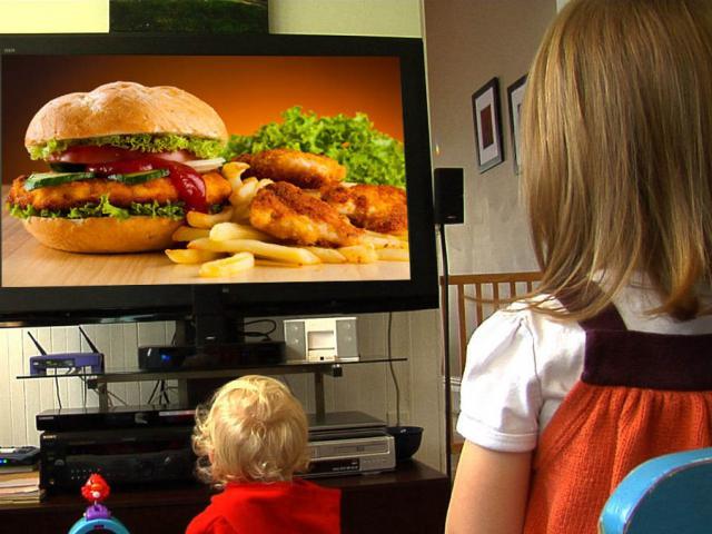 Дети смотрят по телевизору рекламу гамбургеров