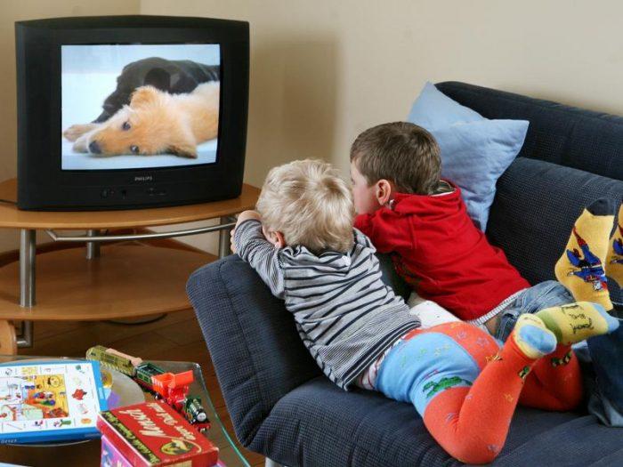 Мальчики лежат на диване и увлечённо смотрят телевизор